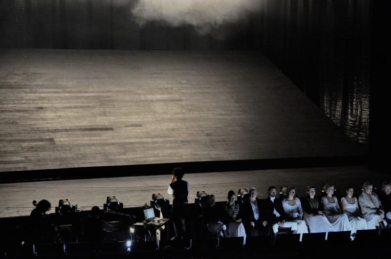 """Sascha Ring singt in Sebastian Hartmanns Inszenierung """"Krieg und Frieden"""", mit dem Rücken zum Publikum, in den Bühnenraum hinein.  Foto: Mai Vendelbo"""