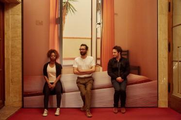 Die Schauspieler*innen Maryam Abu Khaled, Ayham Majid Agha und Dimitrij Schaad. Im Hintergrund: Fotoserie Traumhotels 2012 (Lampedusa) von Sven Ohne. Foto © Judith Buss