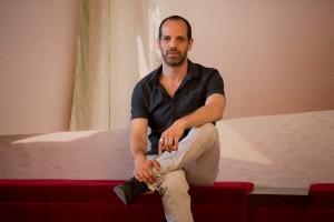 """Der Schauspieler Yousef Sweid. Im Hintergrund die Fotografie von Sven Johne: """"Traumhotels (Lampedusa)"""", Fotoserie 2012. Foto (c) Judith Buss."""