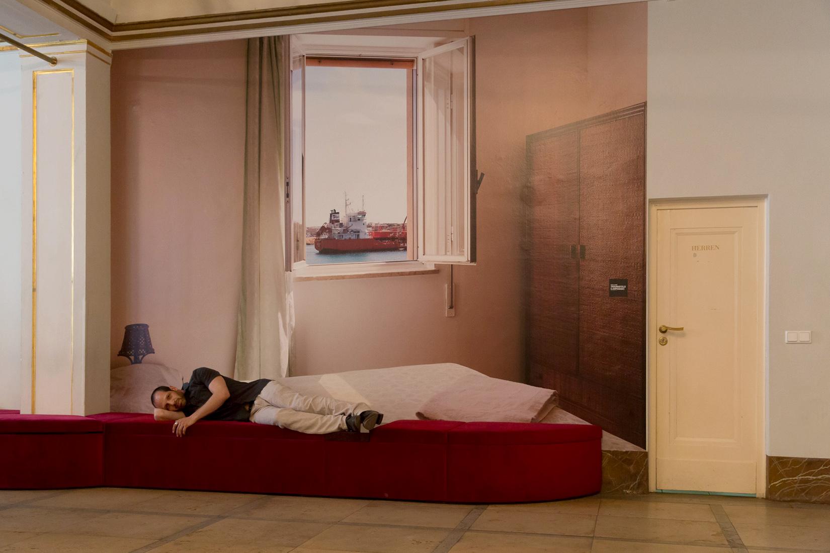"""Der Schauspieler Yousef Sweid im Maxim Gorki Theater. Im Hintergrund die Fotografie von Sven Johne: """"Traumhotels (Lampedusa)"""", Fotoserie 2012. Foto (c) Judith Buss."""