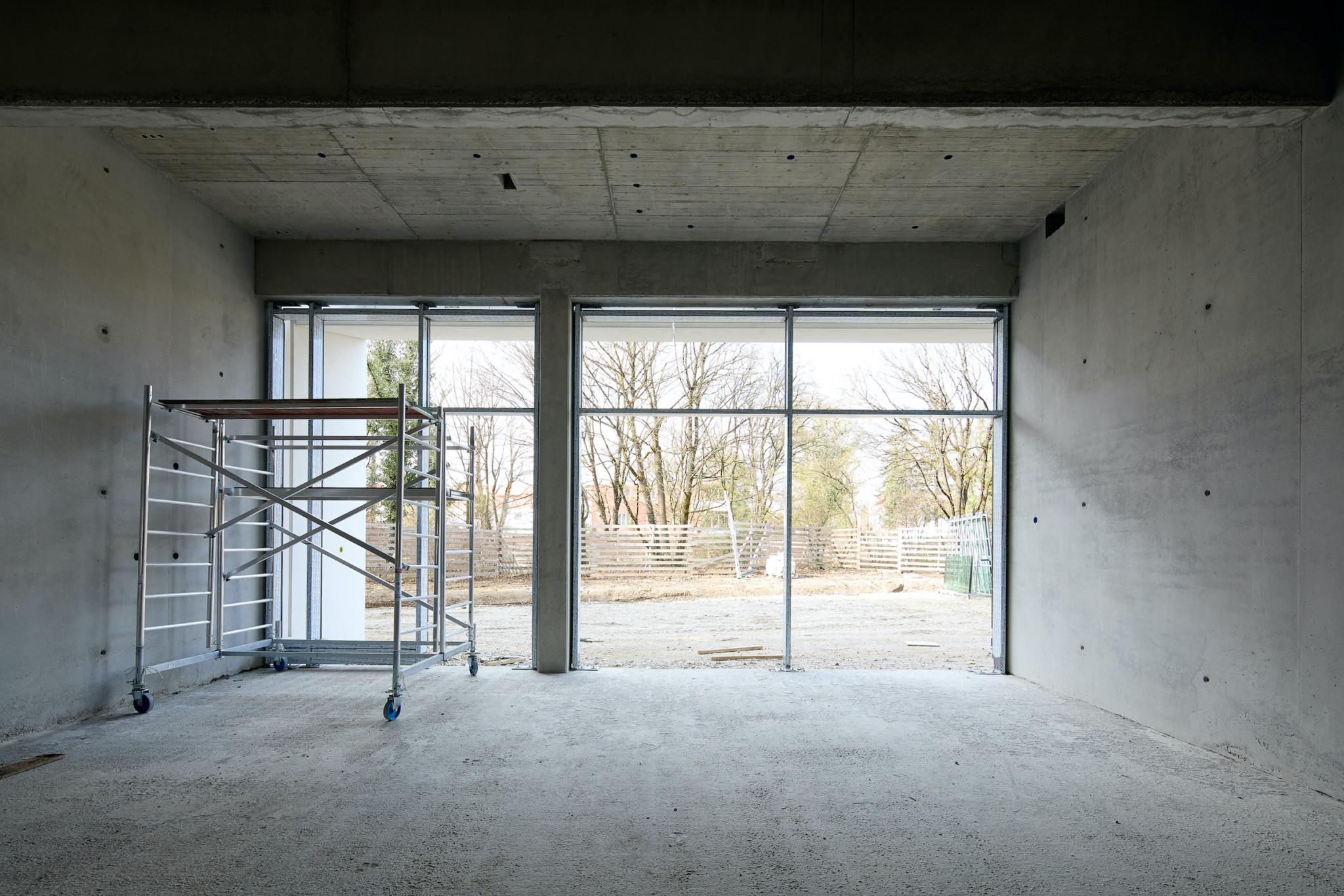 Ein großer leerer Raum im Rohbau. Die raumgroßen Fenster zeigen auf Bäume. Ein Gerüst steht auf der linken Bildseite.