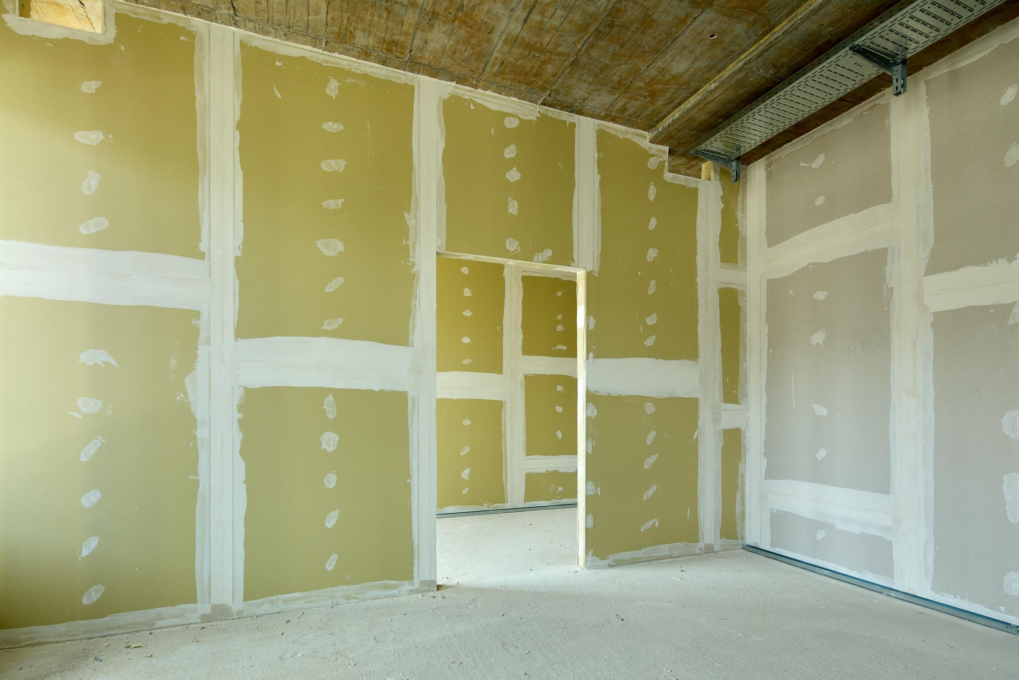 Ein Zimmer im Rohbau. Die Tür in der Bildmitte führt in einen anderen Raum, der ebenfalls sich im Rohbau befindet. Besonders ist, dass der Putz wie Malerie wirkt.