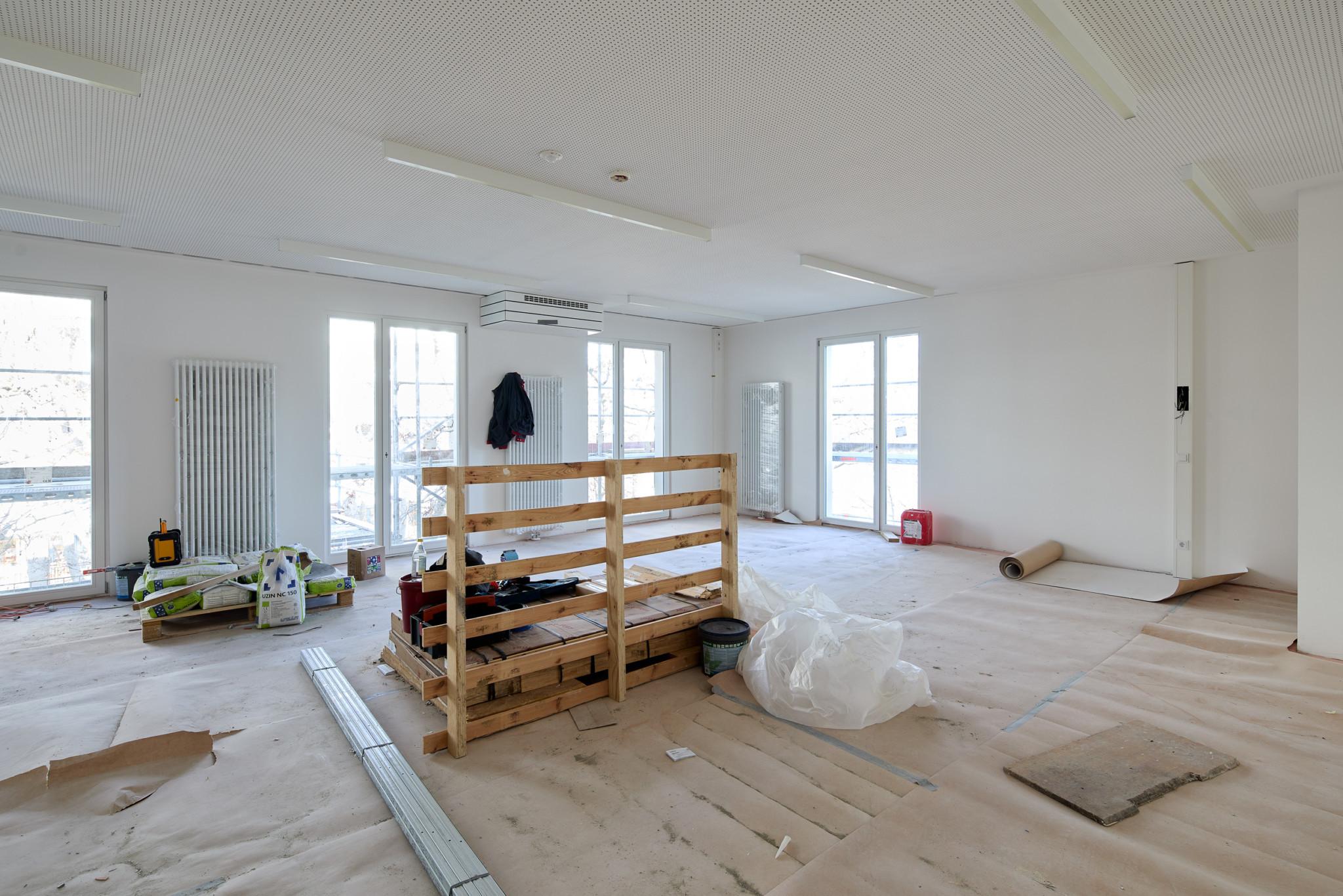 Die Fotografie zeigt ein Zimmer, dessen Wände bereits gestrichen sind, der Boden allerdings noch bedeckt ist von Schutzpapier. Paletten, Zement und Plastikplanen liegen herum.