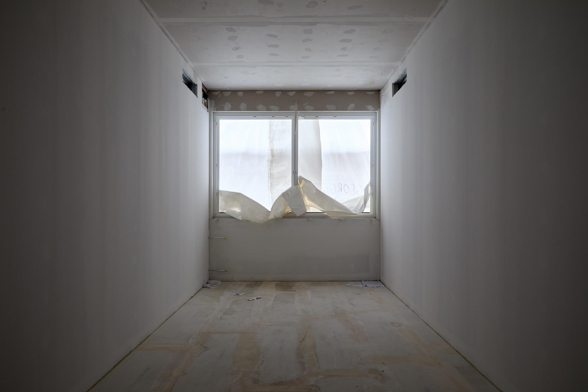 Ein schmales Zimmer, das die Breite eines zweitürigen Fensters hat. Das Fenster ist abgehängt und lässt das Zimmer noch dunkler erscheinen.