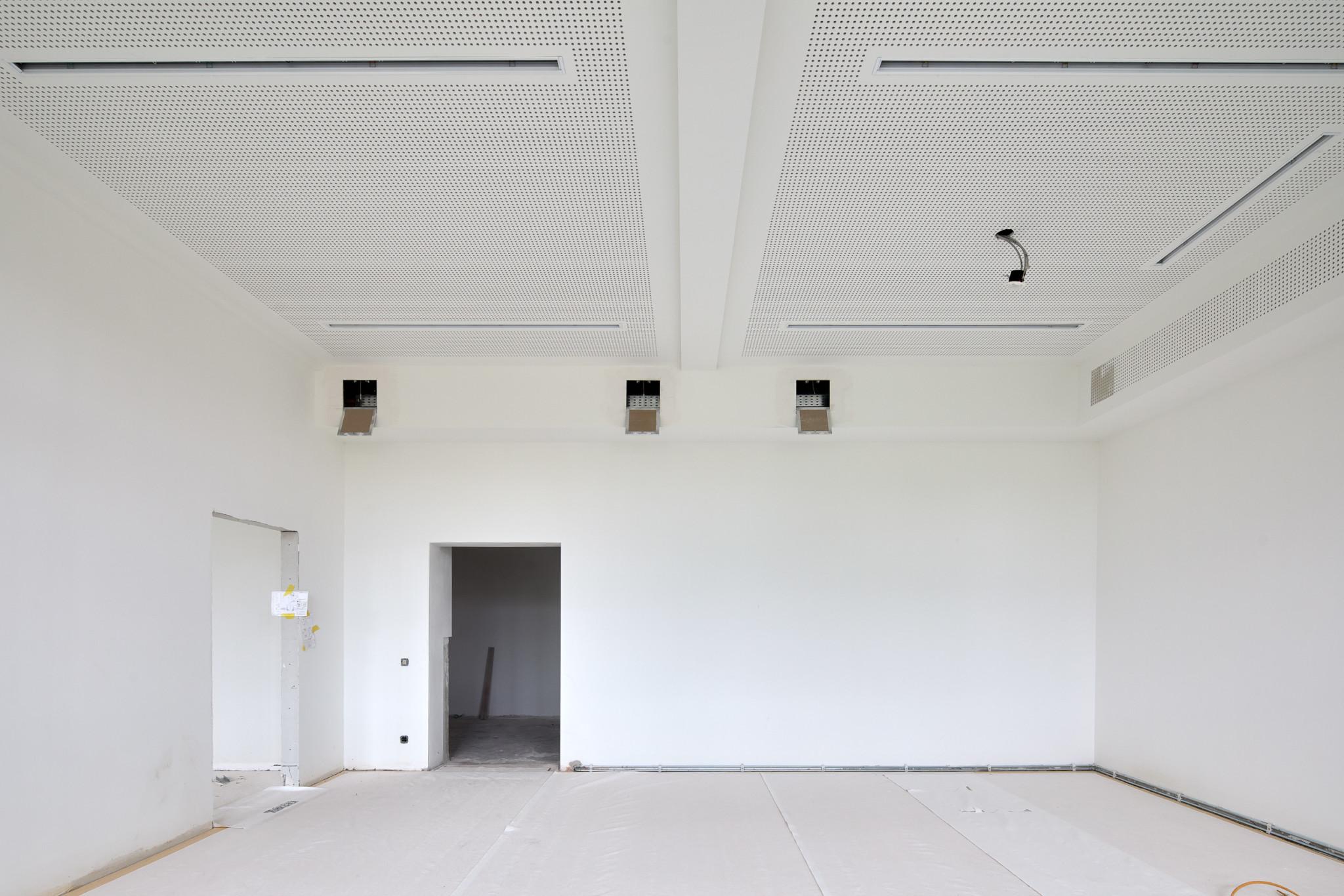 Ein strahlend weißes Zimmer, frisch gestrichen. Einige Dinge fehlen noch: Die Lüftungsschächte sind nicht verschlossen, die Türen noch nicht eingebaut, der Boden noch nicht verlegt.