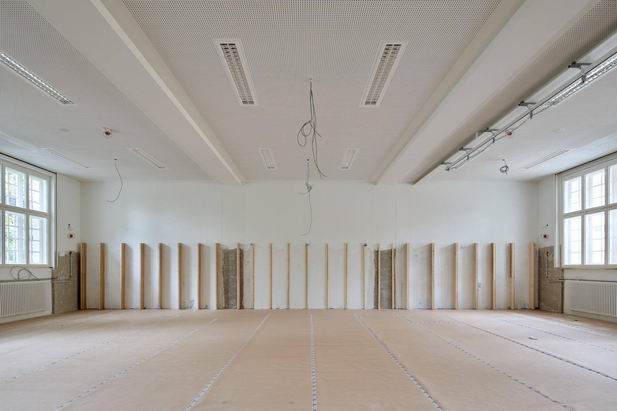 Eine sehr große Halle, komplett leer. Die Kabel hängen von der Decke, der Boden ist noch mit Papierbahnen bedeckt.