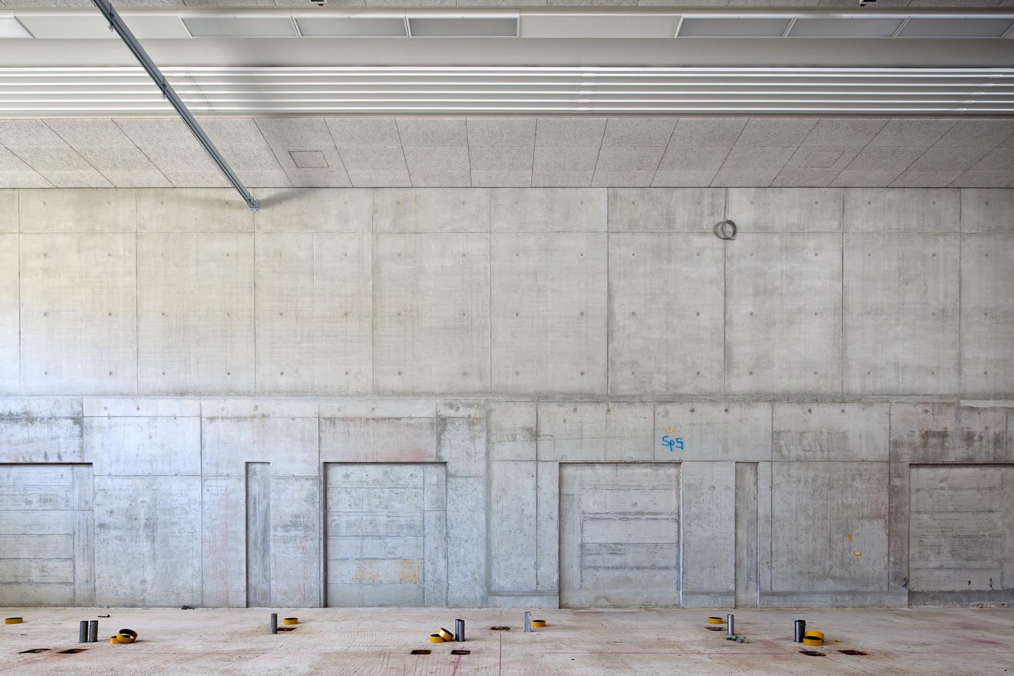 Blick auf einen großen Raum komplett aus Beton gegossen. Der Beton ist noch unverputzt. Auf dem Boden liegen Kleberollen verstreut.