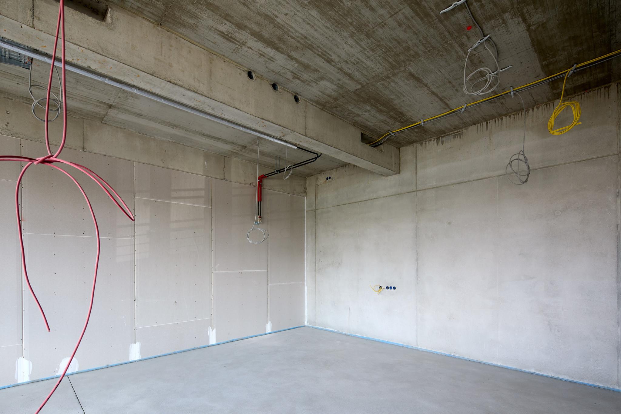 Blick in ein Zimmer, noch unverputzt. Gelbe, rote und graue Kabel hängen von der Decke.