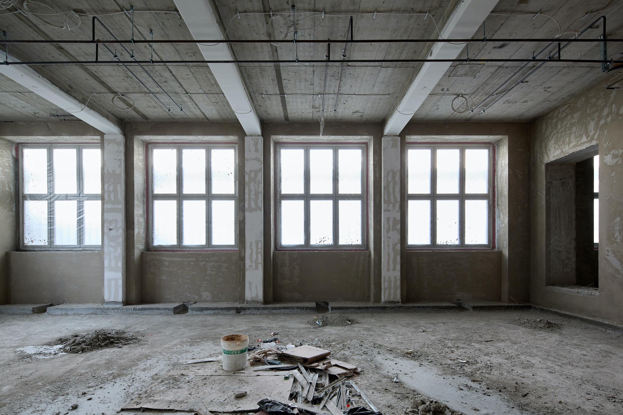 Ein sehr großes Zimmer im Rohbau, auf dem Boden liegt Schutt. Es könnte auch eine verlassene Fabrikhalle sein, wenn man nicht wüsste, dass es neu gebaut wird.