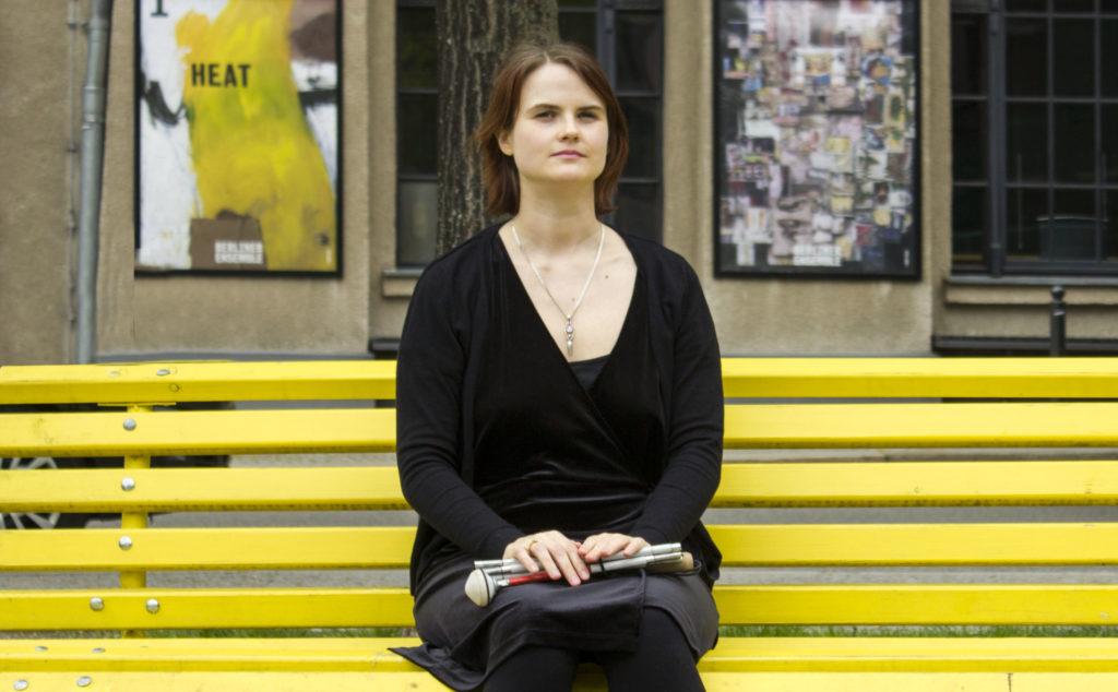 Das Bild zeigt die Gast-Bloggerin Lavinia Knop-Walling, wie sie auf einer Bank sitzt. In ihrem Schoß ein Langstock.