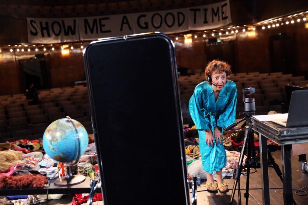 Ein Handybildschirm befindet sich direkt vor der Kameralinse. Dahinter blickt man in einen Theatersaal, von der Bühne aus gesehen. Auf der Bühne steht eine Schauspielerin und schaut in eine Kamera.